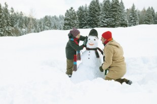 Father and son (8-10) either side of snowman, side view