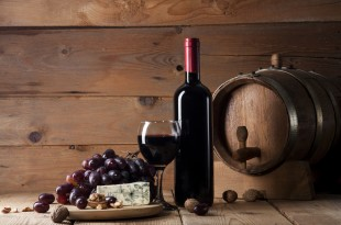 Red wine with blue cheese and ealnuts on wooden background