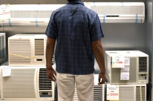 Man looking at air conditioner in supermarket