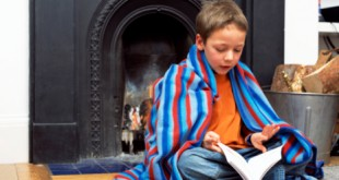 Boy in blanket on floor reading book by fireplace