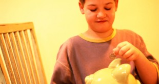 Boy putting coin into piggy bank