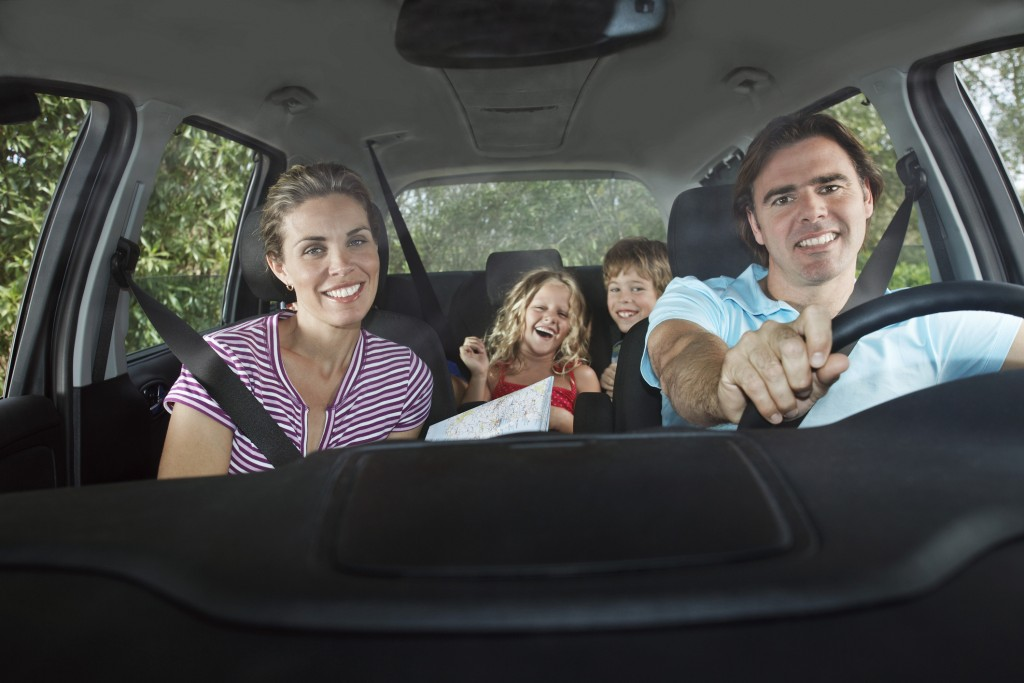 Family with two children (5-6) in car interior, portrait